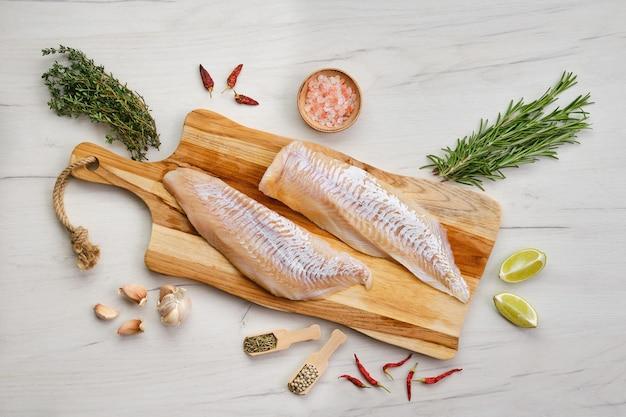 Vista dall'alto di filetto di eglefino con condimento sul tagliere di legno