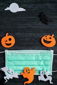 Vista dall'alto del tessuto non tessuto della decorazione del concetto di halloween su sfondo ardesia nero scuro con maschera.