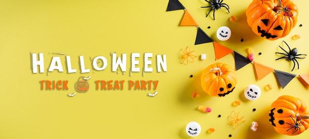 Vista dall'alto di artigianato di halloween, zucca arancione, fantasma, pipistrello e ragno nero su sfondo giallo pastello. vista piana laico e superiore con testo di halloween.