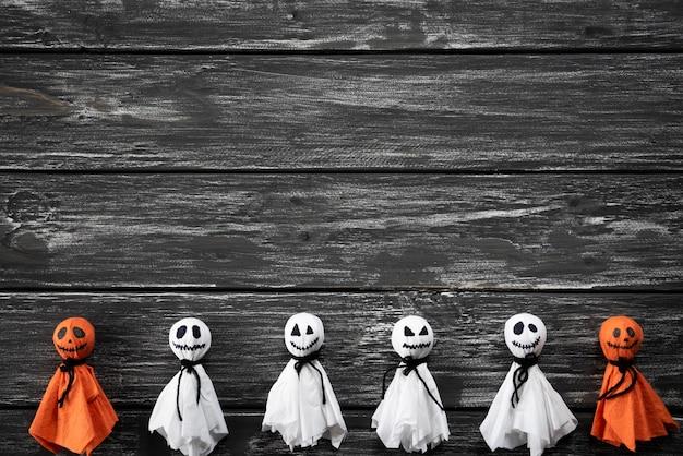 Vista superiore del fantasma di carta bianco e arancio dei mestieri di halloween, su backg di legno in bianco e nero