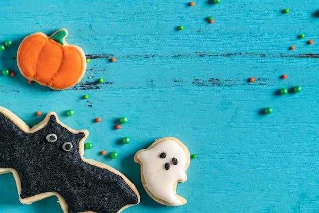 Vista dall'alto dei biscotti di zucchero di pan di zenzero con glassa al forno decorata in festa di halloween su sfondo blu con spazio di copia e disposizione piatta.