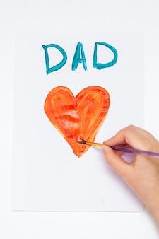 Vista dall'alto della mano del bambino che disegna un cuore rosso con la parola papà biglietto di auguri su carta bianca. concetto di famiglia e festa del papà.