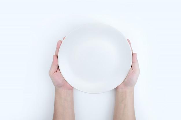 La vista dall'alto della mano tiene in mano un piatto bianco.