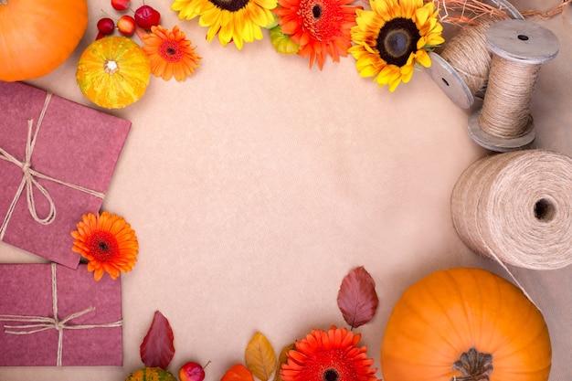 Vista dall'alto della confezione regalo artigianale, fiori gialli e arancioni e zucche su sfondo rosa. biglietto di auguri vuoto per il design del lavoro creativo. posa piatta.