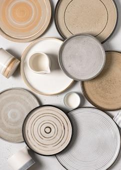 Vista dall'alto di ceramiche fatte a mano, piatti vuoti in ceramica artigianale e tazze su sfondo chiaro.
