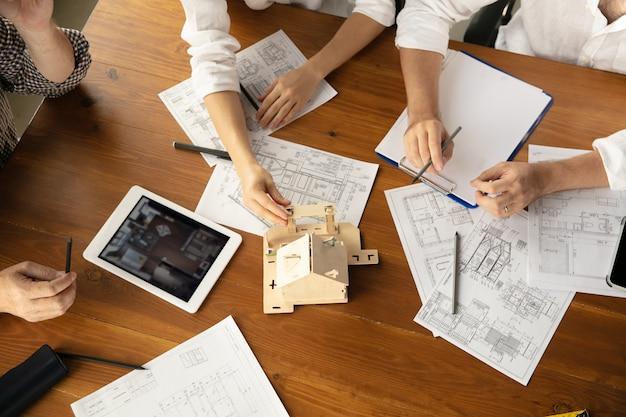 Vista dall'alto mani di architetto-ingegnere e giovane coppia durante la presentazione della futura casa. tabella vista dall'alto con documenti, progetto. prima casa, industriale, concetto di costruzione. trasferirsi in un nuovo luogo dal vivo.