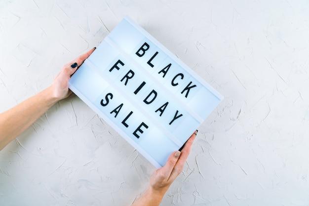 Vista dall'alto delle mani, parole di vendita di promozione del venerdì nero su lightbox tenuto da mani umane. lay piatto