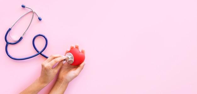 Vista dall'alto delle mani che controllano la forma del cuore con lo stetoscopio e lo spazio della copia