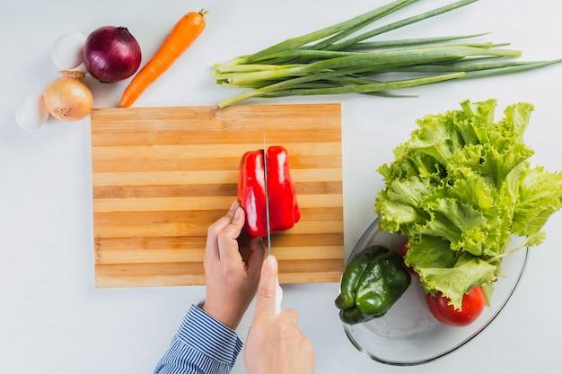 Vista dall'alto delle mani che tagliano il peperone rosso per un'insalata