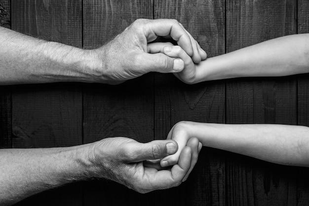 Vista dall'alto, mani di un uomo anziano che tiene la mano di un uomo più giovane. molta consistenza e carattere nelle mani dell'uomo anziano.