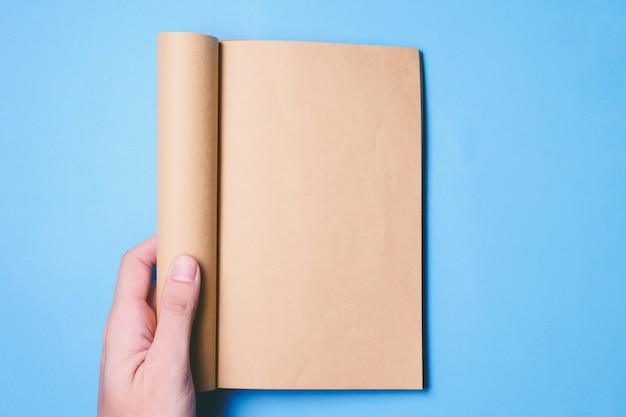 La vista superiore delle mani che tengono un libro in bianco aspetta con lo spazio della copia pronto per testo su fondo blu.