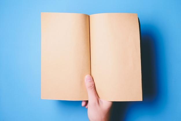 Vista superiore delle mani in possesso di un libro bianco pronto