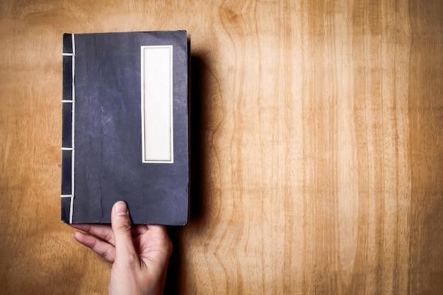 Vista superiore delle mani che tengono un libro su fondo di legno. spazio libero per il testo