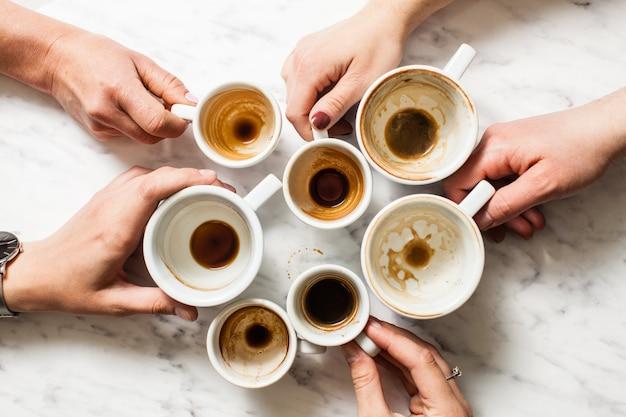 Vista dall'alto mani che tengono tazze di caffè vuote e sporche afterparty