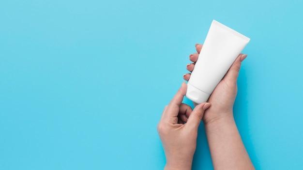 Vista dall'alto delle mani che tengono la bottiglia di gel idroalcolico con lo spazio della copia