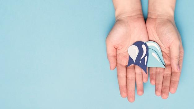 Vista superiore delle mani che tengono le gocce di acqua di carta con lo spazio della copia