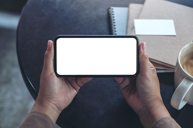 Vista dall'alto mani che tengono e utilizzano un telefono cellulare nero con schermo vuoto in orizzontale per guardare con tazza di caffè e notebook sul tavolo