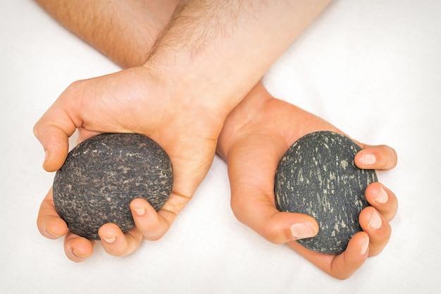 Vista dall'alto delle mani del massaggiatore che tiene massaggio pietre su sfondo bianco