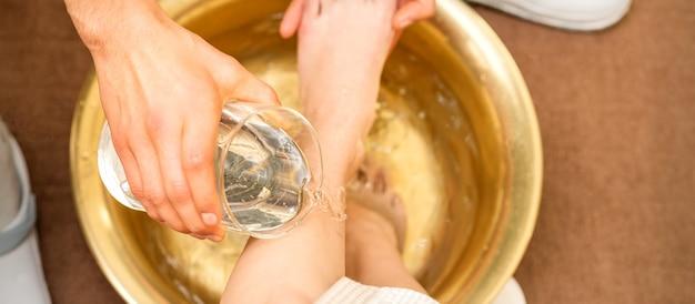 Vista dall'alto delle mani del massaggiatore che lavano le gambe di una giovane donna in una ciotola d'oro al salone di bellezza spa.