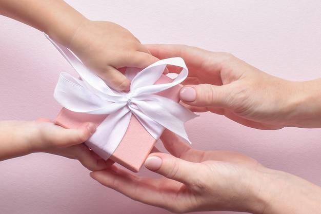 Vista dall'alto delle mani che raggiungono un regalo su uno sfondo rosa. Foto Premium