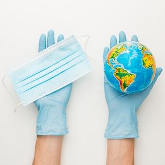Vista superiore delle mani con i guanti che tengono il globo della terra e la mascherina medica