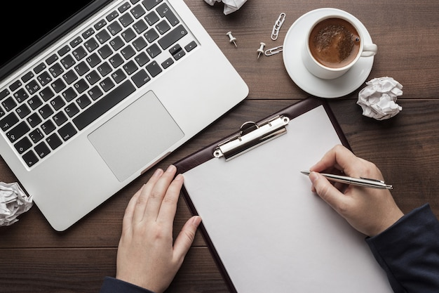 Vista dall'alto delle mani che scrivono sul tavolo dell'ufficio