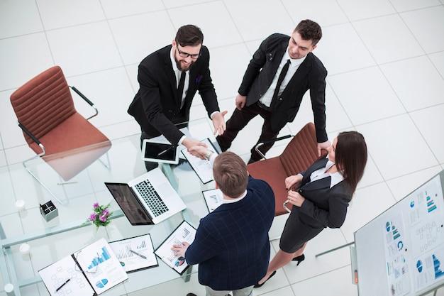 Vista dall'alto - stretta di mano dei partner commerciali prima della presentazione di un nuovo progetto in un ufficio moderno