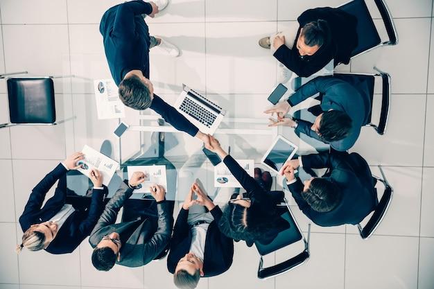 Vista dall'alto. stretta di mano di dipendenti felici in una riunione di lavoro. concetto di affari.