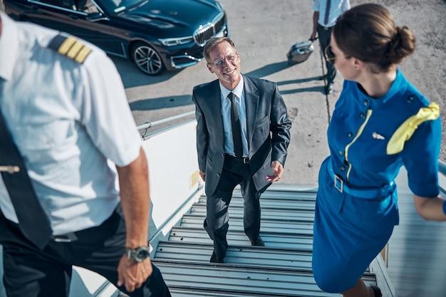 Vista dall'alto di un uomo d'affari felice in tuta che sale le scale per l'aereo insieme a pilota e hostess