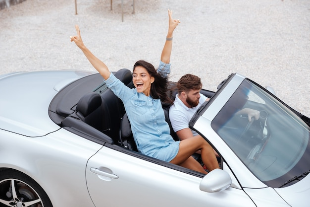 Vista dall'alto di coppia allegra felice che gode del viaggio su strada nella loro decappottabile bianca