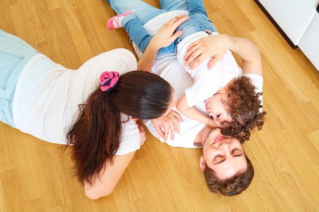 Vista dall'alto di una madre di famiglia felice, padre e figlia sdraiati sul pavimento insieme coccolati riposati felici e soddisfatti