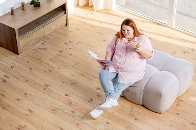 Vista dall'alto di una donna sovrappeso felice che sembra interessata mentre legge una rivista sulla bellezza