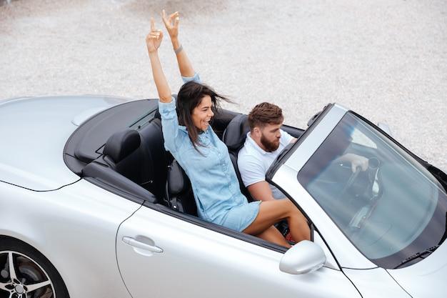 Vista dall'alto di giovani coppie felici che godono del viaggio su strada nella loro decappottabile bianca