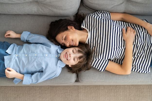 Vista dall'alto sopra di felice giovane mamma e ragazzino rilassante sul divano di casa