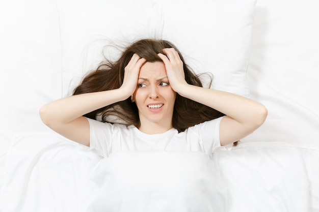Vista dall'alto della testa di una giovane donna bruna stanca sdraiata a letto con lenzuolo bianco, cuscino, coperta. la donna scioccata copre le orecchie con la mano, trascorrendo del tempo nella stanza