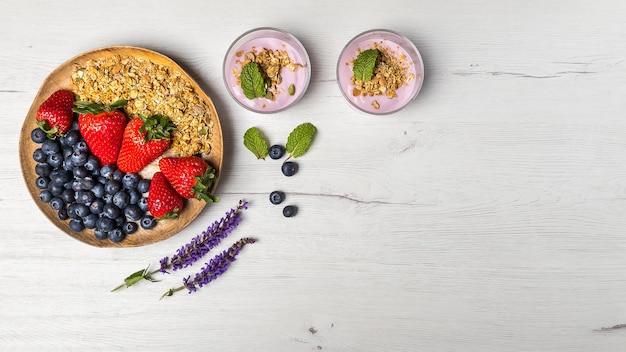 Vista dall'alto di una sana colazione con due ciotole di yogurt ai frutti di bosco con muesli e avena e un piatto di legno di fragole e mirtilli