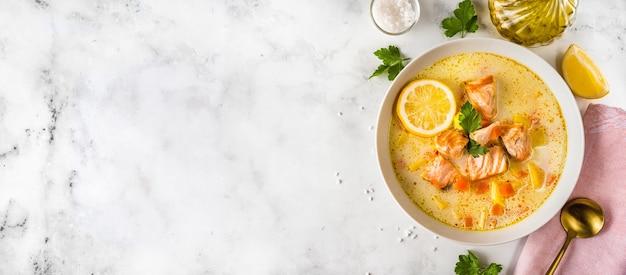 Vista dall'alto di una sana zuppa di salmone cremoso in un piatto sulla superficie bianca. alimenti dietetici. copia spazio. banner lungo
