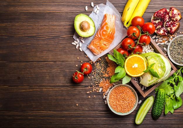 Vista dall'alto di una dieta sana ingredienti alimentari in una scatola di legno: verdure, fagioli, frutta, pesce, erbe aromatiche con spazio per il testo, fondo di legno rustico.