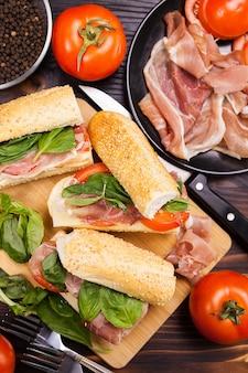 Vista dall'alto su panini sani accanto agli ingredienti di cui era fatto su un tavolo di legno