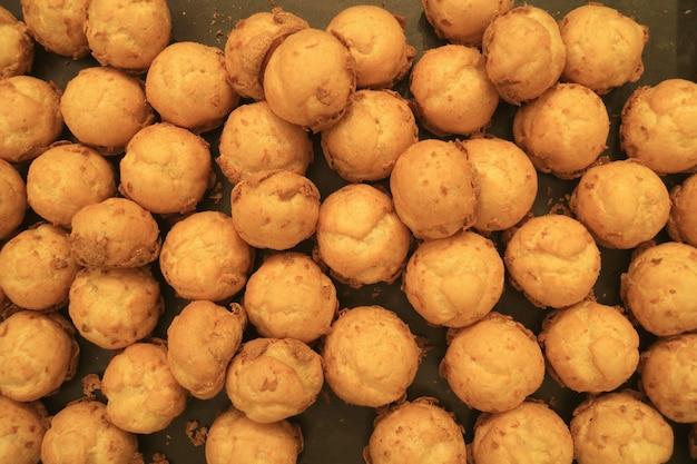 Vista dall'alto di un mucchio di palline di pasta choux francese appena sfornate prima di essere riempite con la crema