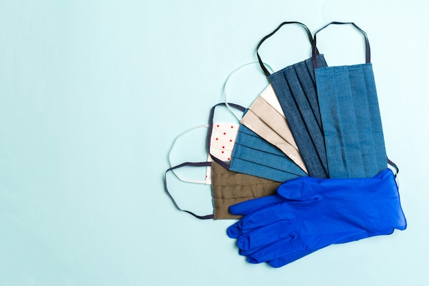 Vista dall'alto di un mucchio di maschere di cotone fatte in casa e guanti di nitrile sulla superficie blu