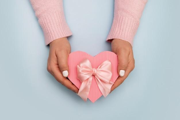 Vista dall'alto della confezione regalo a forma di cuore in mani femminili sulla superficie colorata