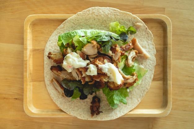 Vista superiore del kebab di pollo fatto in casa sul piatto di legno.