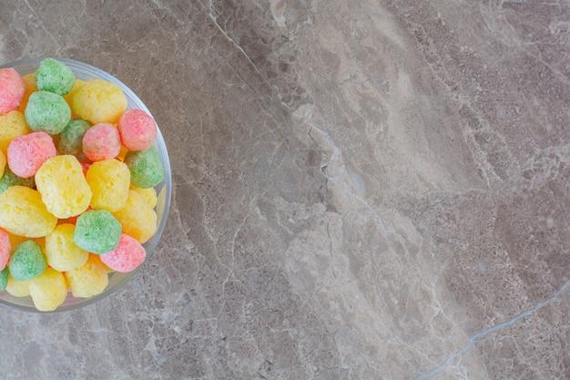 Vista dall'alto di caramelle colorate fatte in casa in una ciotola su grigio.