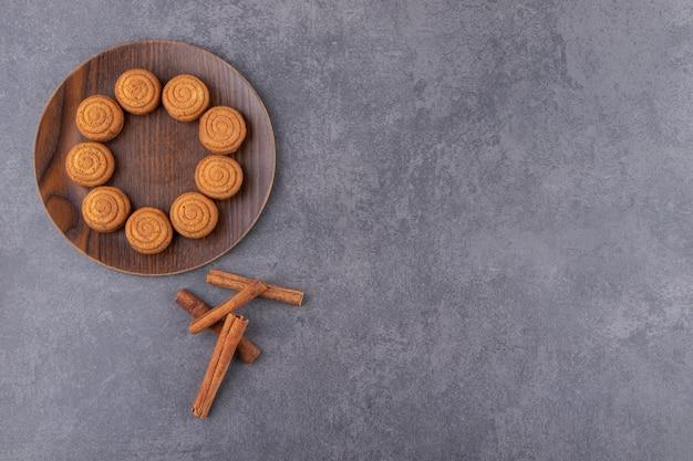 Vista dall'alto di biscotti fatti in casa con cannella sul piatto di legno.