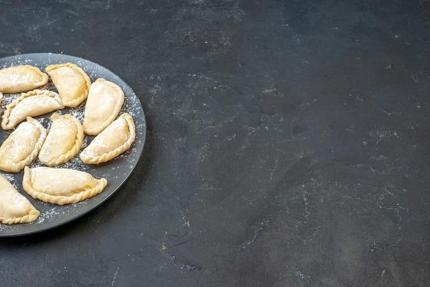Vista dall'alto di gnocchi crudi fatti in casa su un piatto sul lato destro