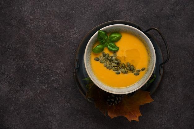 Vista dall'alto della calda zuppa di zucca autunnale con semi di zucca su sfondo scuro strutturato