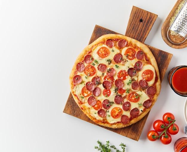 Pizza ai peperoni italiana fatta in casa calda vista dall'alto con salame, mozzarella sul tavolo bianco