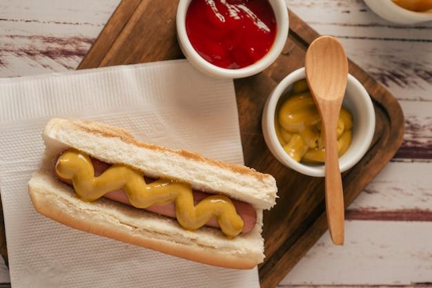 Vista dall'alto di un hot dog con senape su una tavola di legno con pentole con ketchup e senape. concetto di fast food.