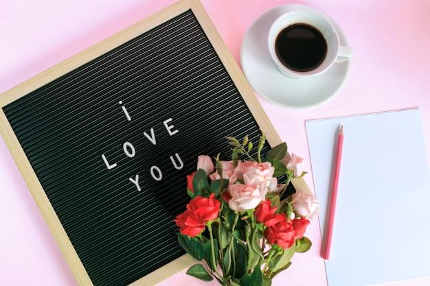 Vista dall'alto di ti amo sulla bacheca con una tazza di caffè, rose e matita su carta bianca isolata su sfondo rosa